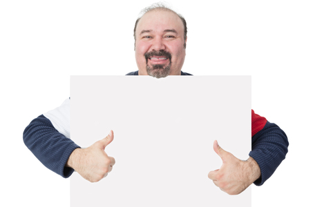 Happy smiling middle-aged man with a goatee holding a blank white board with copyspace for your text giving a thumbs up gesture of approval photo