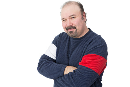 introspective: Portrait of a balding mature man with arms crossed on a white background