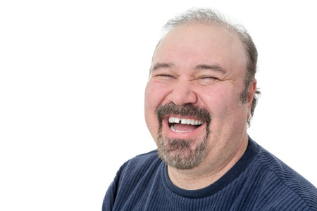 chuckling: Close-up portrait of a funny mature man laughing hard on a white background