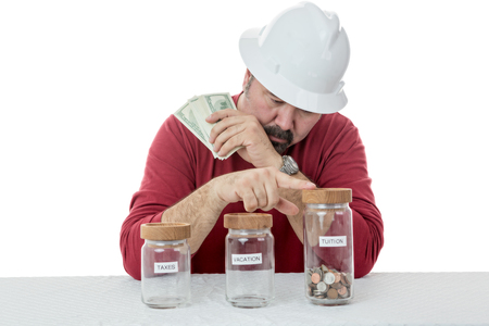 frugal: Construction worker wearing a hardhat deciding over the use of money between, taxes, vacations or tuitions