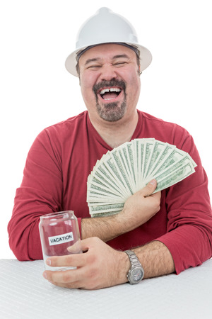 fanned: Construction worker laughing with joy holding to vacations money Stock Photo