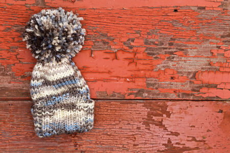 Cute warm woolen winter hat with a large pompom lying on an old wooden picnic table with a grungy surface of peeling red paint with copyspace for your text photo