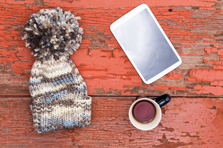 winter fashion: Woolly winter cap with a large decorative pompom lying with a tablet computer and mug of fresh tea on a grungy wooden table with peeling paint Stock Photo
