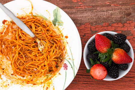 Overhead view of a messy plate of spaghetti Bolognese in a rich tomato sauce and fresh berry dessert with strawberries and blackberries on a grungy old wooden table with peeling paint photo