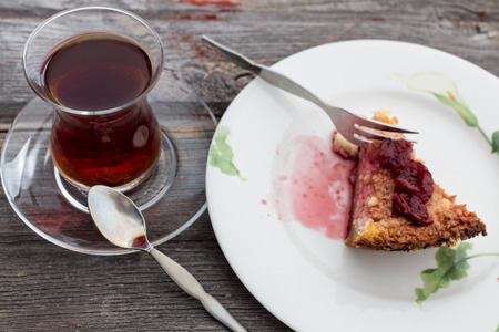 glass topped: Slice of delicious cheesecake topped with a berry compote and served with a tall glass of freshly brewed Turkish tea on an old wooden table
