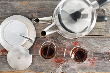 teaset: View from above showing the preparation of two hot glasses of Turkish tea using the traditional stacked kettles on an old rustic wooden table top Stock Photo