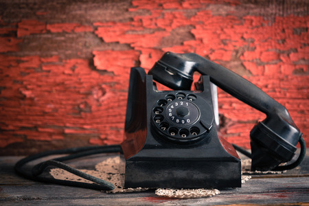 Old-fashioned rotary telephone with the handset off the hook effectively blocking the line against a rustic wall with distressed peeling red paint photo