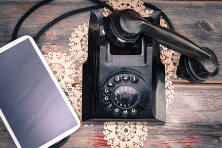 Tablet computer with a blank screen lying alongside a retro rotary telephone with its handset off the hook on a decorative doily, high angle view photo