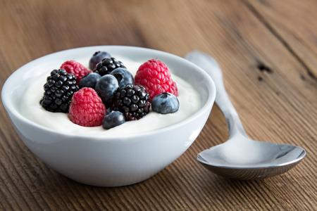 Kom van verse gemengde bessen en yoghurt met boerderij verse aardbeien, bramen en bosbessen geserveerd op een houten tafel