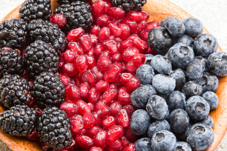Closeup of juicy mixed berries and succulent pomegranate seeds in a wooden bowl with blackberries and blueberries for a healthy dessert rich in antioxidants