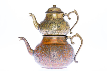 Isolated antique engraved copper Turkish teapot with double stacked kettles allowing tea to be brewed in one while hot water from the larger kettle is used to dilute individual cups of tea to taste photo