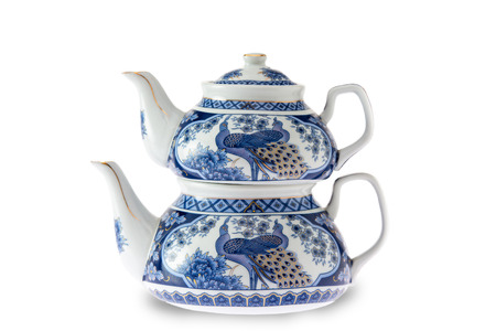 teaset: Antique pottery Turkish teapot with the traditional double stacked kettles decorated with a blue and white design depicting a peacock, over a white background