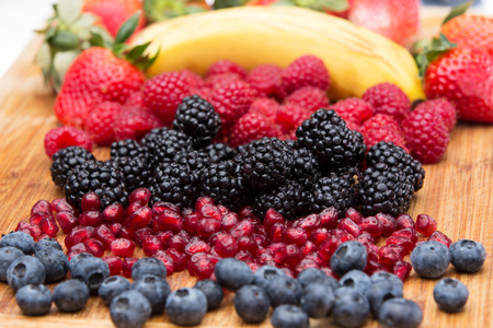 Assorted freshly washed fruit in the kitchen arranged on a wooden countertop in colourful rows with blueberries, blackberries, pomegranate seeds, raspberries, strawberries and a fresh banana photo