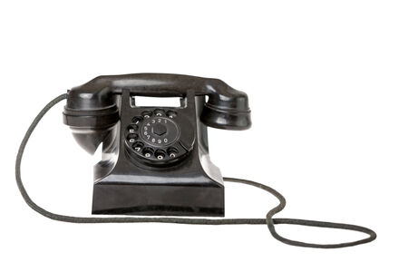 Old-fashioned black rotary telephone instrument with its handset on the cradle on a white background with a reflection and copyspace photo