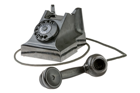 Retro dial-up rotary telephone with the handset lying in the foreground turned towards the camera on a white studio background photo