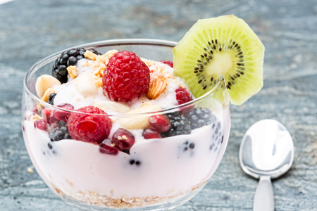 Closeup of a glass of delicous frozen berry parfait containing blackberries raspberries, pomegranate seeds and almonds, garnished with a slice of kiwifruit photo
