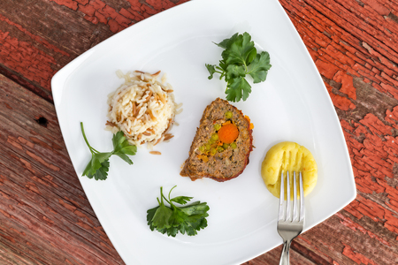 Vegetable stuffed meatloaf served with rice pilaf and mashed potato, garnished with parsley on picnic table photo