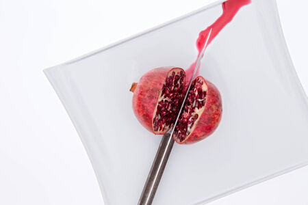 pulpy: Fresh pomegrate being cut in half with a knife on a white plate with sweet juice running out as the pulpy seeds or arils or exposed, overhead view