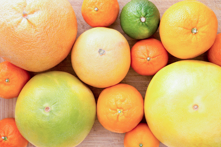 clementine fruit: Background of assorted citrus fruit with lemon, lime, orange, tangerine, clementine and grapefruit, close up view from above on a wooden background