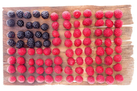 Unusual geometric background pattern of fresh healthy autumn or fall berries arranged in rows to form a rectangle of ripe red raspberries with an inset square of blackberries Stock fotó