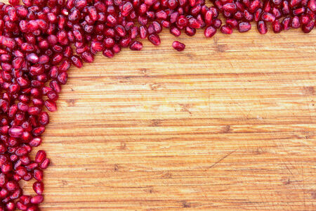 Border of fresh ripe red pomegranate seed on a textured wood background arranged in a pile in the top left corner with ample copyspace for your text or menu Stok Fotoğraf