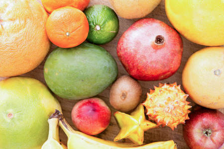 Background of assorted citrus fruit with lemon, lime, orange, tangerine, clementine and grapefruit, close up view from above on a wooden background photo