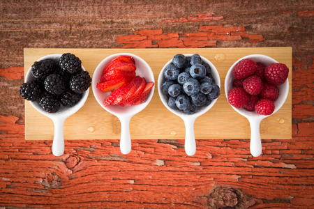 snack: Fresh assorted berries on a grungy wooden counter displayed in small ceramic ramekins including blackberries, blueberries, strawberries and raspberries for a healthy snack or appetizer