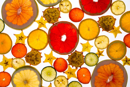 Vibrant background of translucent sliced fresh fruit neatly arranged on a white background with a variety of citrus, carambola or star fruit and kiwano or horned melon photo