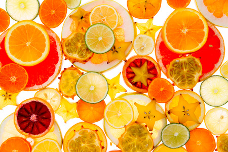 Healthy vibrant tropical fruit and citrus background of sliced orange, lemon, lime, a variety of grapefruit, carambola or star fruit and kiwano or horned melon, symbolic of vitality and health photo