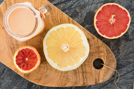 pomelo: Freshly prepared grapefruit juice with halved ruby and ordinary grapefruit used as ingredients on an old olivewood cutting board with decorative grain , view from above on a stone counter Stock Photo
