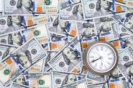 proceeds: Conceptual financial background of American 100 dollar bills with Benjamin Franklinf facing upwards and a vintage watch depicting time