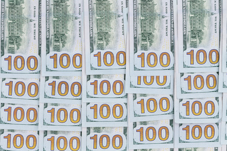 Neatly arranged background of American 100 dollar bills with all the numbers aligned in rows in a conceptual financial background, overhead view