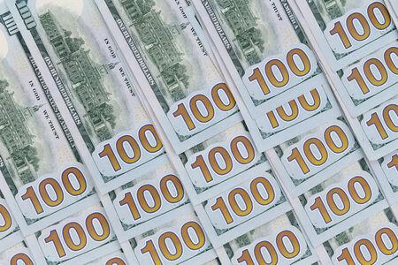 dinero falso: 100 billetes en dólares americanos bien ordenados boca abajo con los números de denominación alineados en un patrón diagonal en un fondo financiero y monetario conceptual