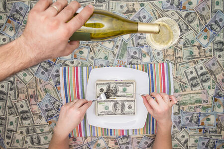 magnificence: Man eating dollar bills as a servant pours champagne from a bottle overhead on a background of money in a conceptual image of wealth and extravagance