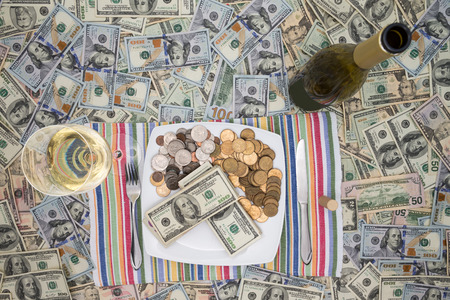 surfeit: Conceptual financial image of a plate of money with cutlery flanked by a bottle and glass of champagne on a background of 100 dollar bills depicting eating money through greed and extravagance