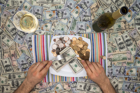 surfeit: Conceptual image of a man eating money through extravagance with an overhead view of him sitting at a table covered in 100 dollar bills eating money on a plate with a glass and bottle of champagne Stock Photo