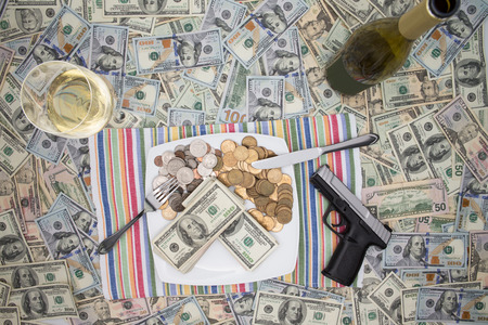 surfeit: Overhead view of a place setting with a plate of money, a handgun and champagne on 100 dollar bills depicting wealth through crime and racketeering or celebrating a win and keeping it secure
