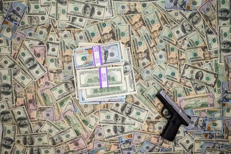 proceeds: Conceptual image of the monetary proceeds of criminality with a handgun lying on a background of 100 dollar American bills alongside a pile of cash