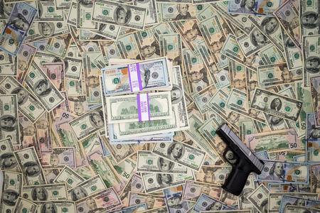 proceeds: Imagen conceptual de los ingresos monetarios de la criminalidad con una arma de mano situada sobre un fondo de 100 billetes de d�lar americano, junto con un mont�n de dinero en efectivo