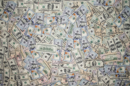 surfeit: Multiple scattered American 100 dollar banknotes in full frame coverage with corner vignetting viewed from above in a conceptual financial background