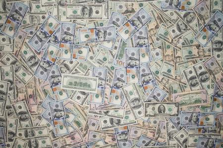 dinero falso: Varios billetes de 100 dólares estadounidenses esparcidas en la cobertura de fotograma completo con esquina viñeteado se ve desde arriba en un fondo financiero conceptual