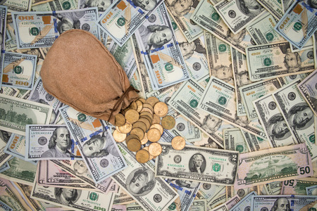 surfeit: Background of American 100 dollar banknotes scattered randomly completely covering the surface with a hessian bag of spilling dollar coins on top of it, overhead view