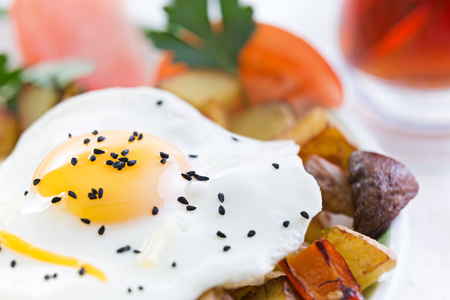 cholesterol free: Nutritious fried egg served sunny side up with healthy fresh vegetables including diced potatoes and mushrooms with tomato garnished with fresh parsley Stock Photo