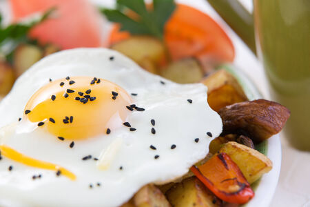 sunny side up: Wholesome meal of a delicious sunny side up fried egg with a rich yellow yolk and vegetables including potatoes, sliced tomato and mushrooms, high angle closeup view Stock Photo