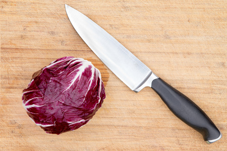 radicchio: Overhead view of a single cleaned whole raw red radicchio displayed with a kitchen knife on an old bamboo cutting board with copyspace during preparation in the kitchen