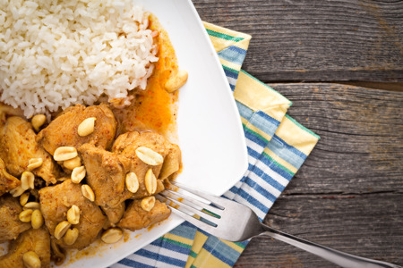 Traditional homemade Thay food made of chicken meat, rice, curry, spicy aromatic sauce and roasted peanuts, on a plate, on a rustic wooden table