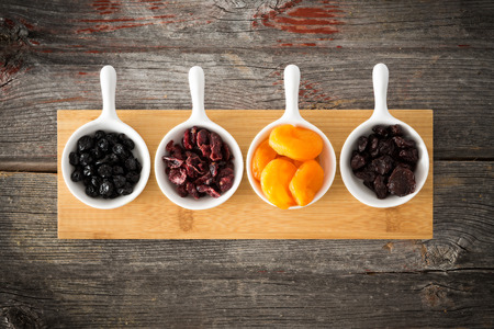 sour cherry: Small ceramic dishes of dried cranberries, apricot, blueberries and cherries arranged in a row on a wooden board on an old weathered wood surface for a healthy snack or tasty appetizer, overhead view Stock Photo