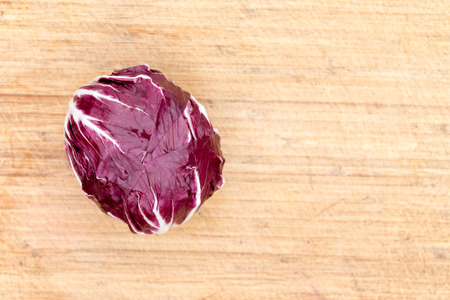 radicchio: Overhead view of a single red radicchio rich in anthocyanin on a bamboo cutting board with copyspace