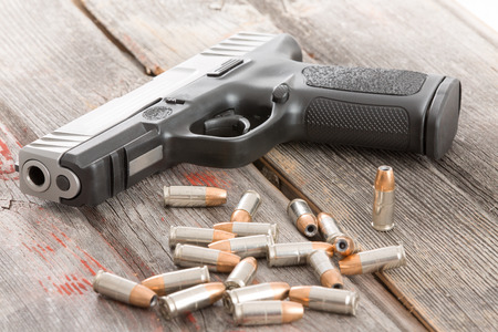 heist: Handgun and a pile of scattered bullets lying on an old rustic wooden table  Stock Photo