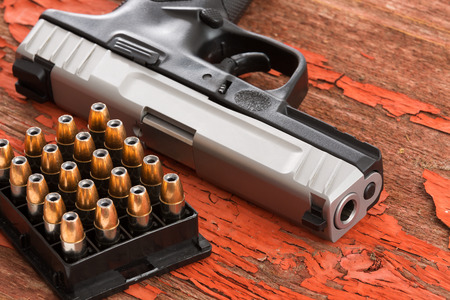 Close up of the barrel of a handgun and full rack of ammunition lying on a grungy wooden surface